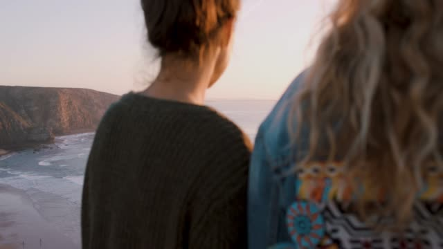 vídeos de stock e filmes b-roll de two women on a cliff watching the sunset together - baía