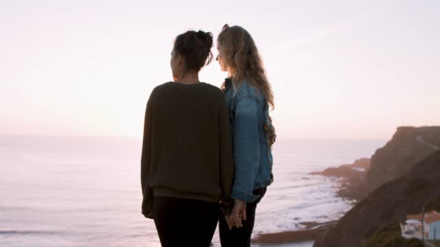 Two women on a cliff watching the sunset together