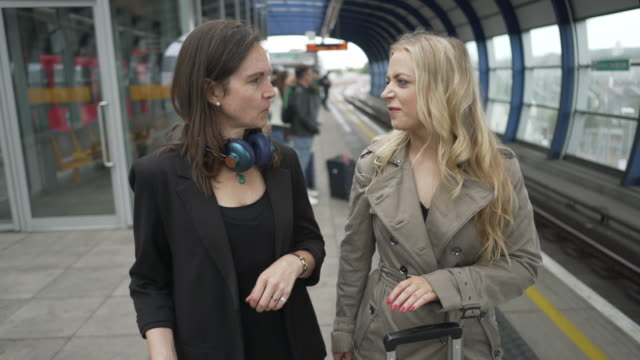 two women on a train platform waiting for a train - railway station stock videos & royalty-free footage