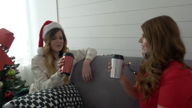 two women on couch talking as then drink from coffee cups - coffee drink stock videos & royalty-free footage
