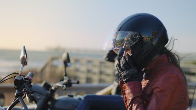 MS SLO MO. Two women on motorcycles take helmets off and shake hair free in the wind overlooking the ocean.