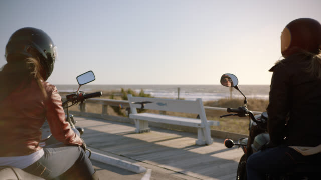 vídeos de stock e filmes b-roll de slo mo. two women on motorcycles watch as birds land on scenic boardwalk and take off overlooking the ocean. - casaco curto com mangas