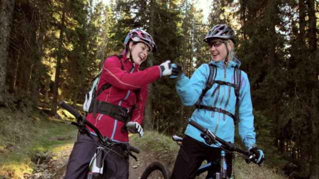 two women on mountain bikes doing a fist bump in the forest - sports helmet stock videos & royalty-free footage