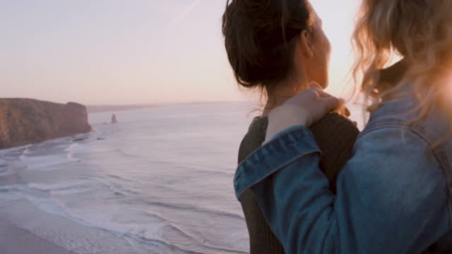 two women on sea cliff at sunset - reportage stock videos & royalty-free footage