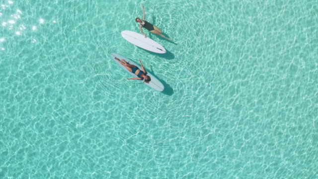 two women on surfing boards, enjoying ocean in maldives - swimming costume isolated stock videos & royalty-free footage