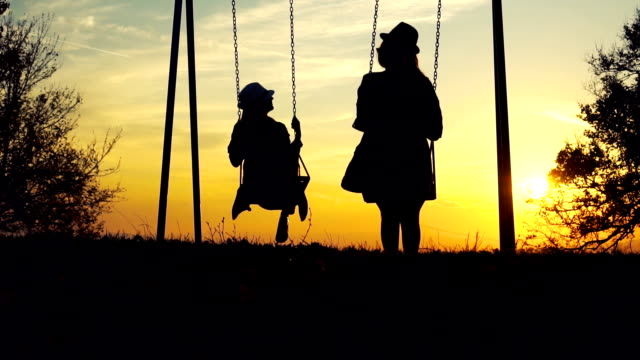 Two women on swing looking at sunset