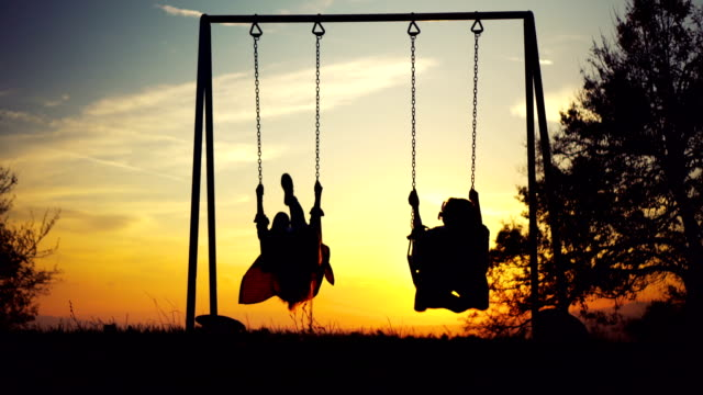 two women on swing looking at sunset - swinging stock videos and b-roll footage