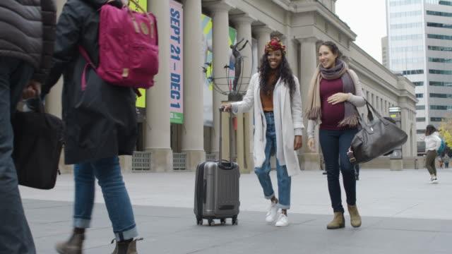 都市の歩道を歩く休暇中の2人の女性 - 人間の消化器官点の映像素材/bロール