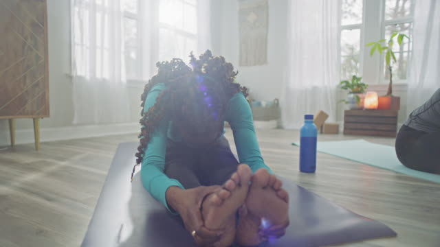 vídeos de stock e filmes b-roll de slo mo. two women on yoga mats lean forward and hold their feet in seated forward fold stretch. - curvar se