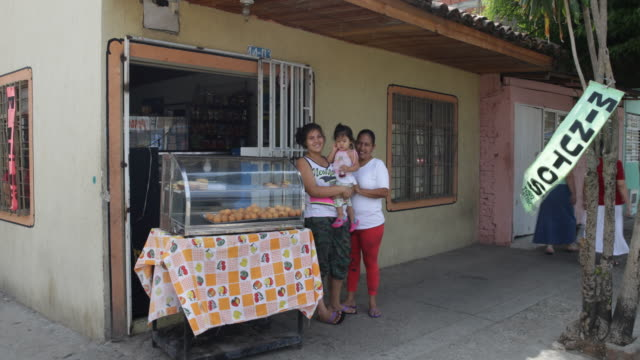 two women, one holding a baby girl, standing next to a display cabinet in front of a little shop on a street corner in el vertel, a neighborhood with... - display cabinet stock videos & royalty-free footage