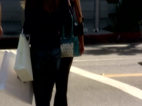vídeos de stock, filmes e b-roll de two women one wearing high heels one carrying shopping bags cross road in beverly hills - jeans calça comprida