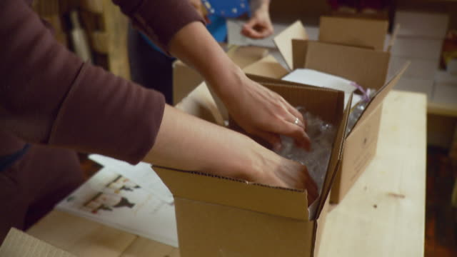 vidéos et rushes de ms ha two women packing cardboard boxes on table in shop/ burlington, vermont, usa. - buste partie du corps