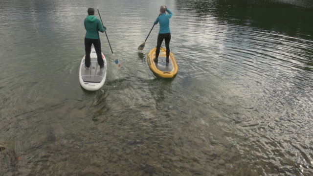 Two women paddleboard across mountain lake