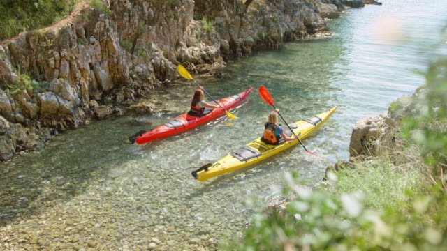two women paddling their sea kayaks out of the small inlet in sunshine - 40 49 years stock videos & royalty-free footage
