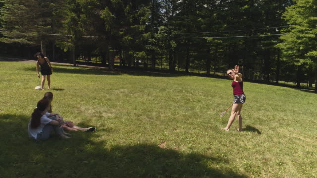 two women playing badminton on the lawn, and their daughters watching the game. top view directly above, aerial drone video - lawn stock videos & royalty-free footage