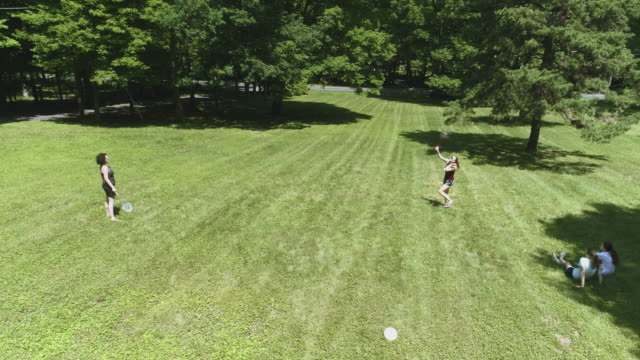 Two women playing badminton on the lawn, and their daughters watching the game. Top view directly above, aerial drone video