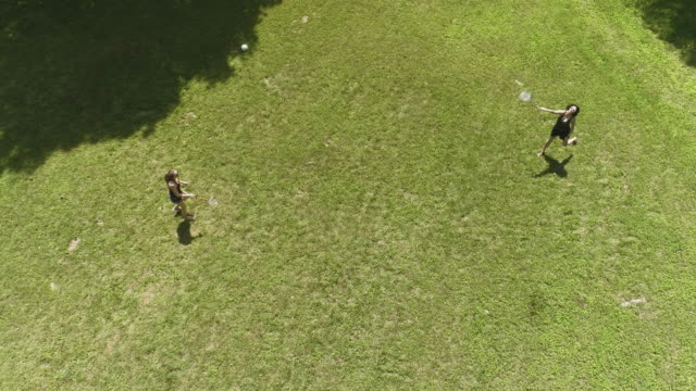 vídeos de stock, filmes e b-roll de duas mulheres jogando badminton no gramado. menina de adolescente trazendo o chapéu para a mãe dela. vista superior diretamente, zangão aéreo vídeo acima - badmínton esporte