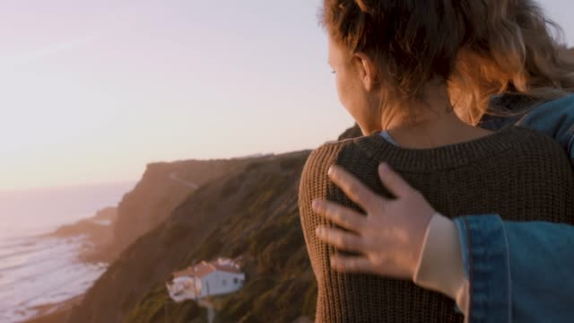 two women playing, hugging on a cliff at sunset - umarmen stock-videos und b-roll-filmmaterial