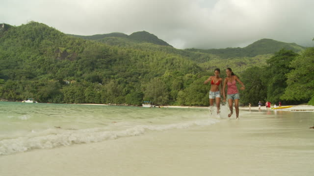 ws two women playing in ocean waves / seychelles - ärmelloses oberteil stock-videos und b-roll-filmmaterial
