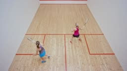Two women playing squash in a nice new court
