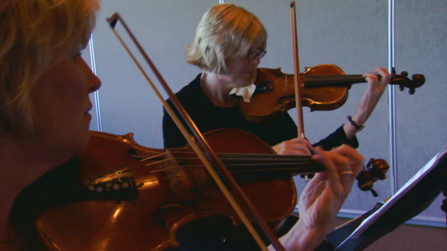 Two women playing violins