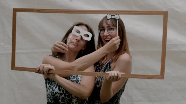 two women pose with photo frame and props - bow pose stock videos & royalty-free footage