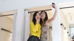 Two women posing for camera phone in changing room
