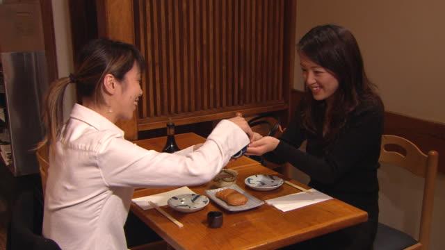 ms, two women pouring sake in japanese restaurant - 対面点の映像素材/bロール