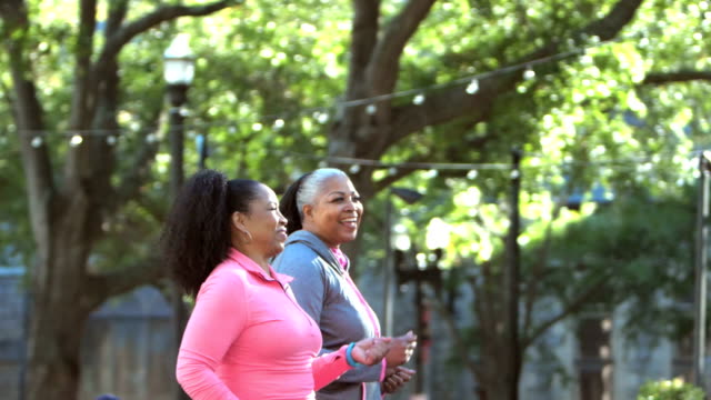 two women power walking in the city, talking and smiling - city life stock videos & royalty-free footage