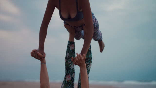 Two women practicing acroyoga on the beach at dusk/dawn at Atlantic ocean beach in France