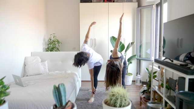 two women practicing yoga at home - mid length hair stock videos & royalty-free footage