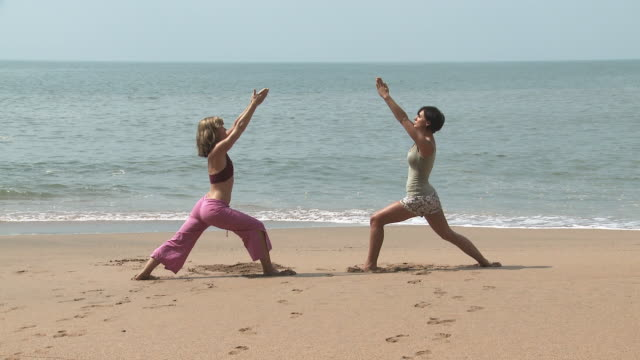 Two women practicing yoga by the ocean