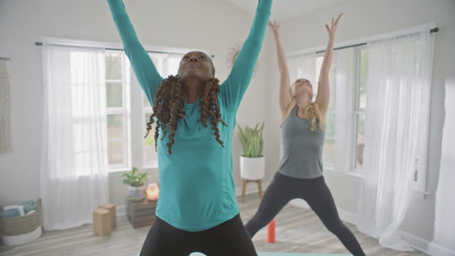 slo mo. two women practicing yoga in home studio straighten out of wide legged forward fold into wide legged raised arm mountain pose. - mountain pose stock videos and b-roll footage