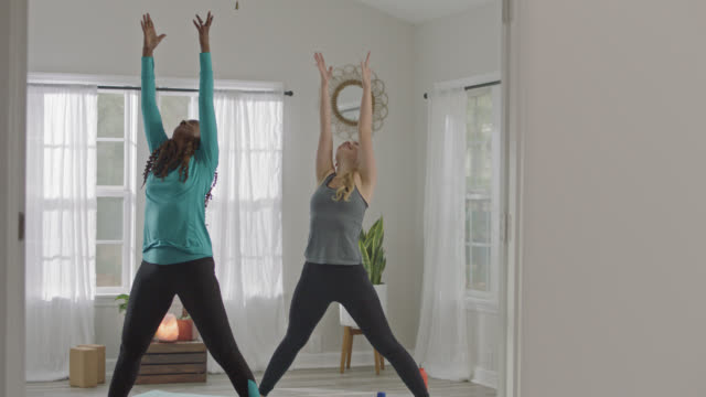 slo mo. two women practicing yoga in home studio wave hands in the air in wide legged raised arm mountain pose. - mountain pose stock videos and b-roll footage
