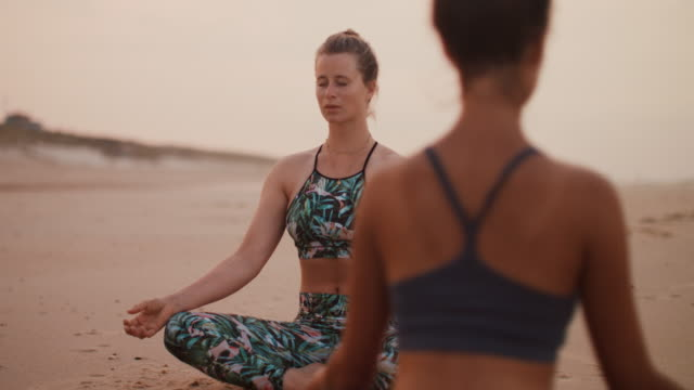 two women practicing yoga/meditating on the beach at sunset in france - strength stock videos & royalty-free footage