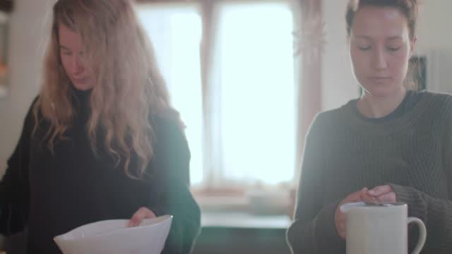 vidéos et rushes de two women preparing breakfast in the morning in kitchen - deux personnes