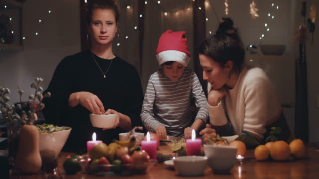 two women preparing christmas dinner with young boy - algarve stock-videos und b-roll-filmmaterial