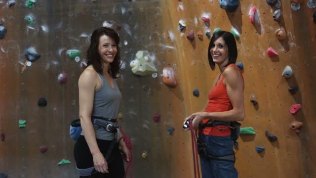 two women preparing to climb an indoor climbing wall