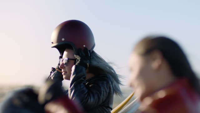 MS SLO MO. Two women pull on motorcycle helmets on road trip.