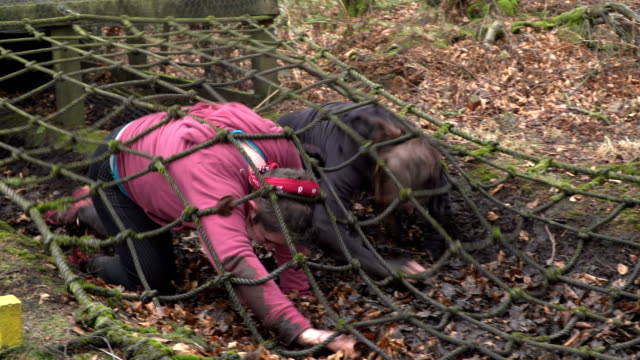 4k: two women racing through netting tunnel on assault course / obstacle course - crawling stock videos and b-roll footage