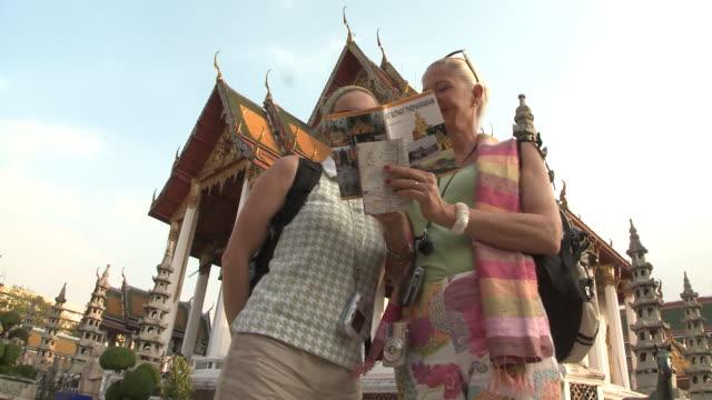 MS LA Two women reading guidebook at Wat Phra Kaew (Temple of the Emerald Buddha), Bangkok, Thailand