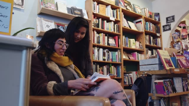 two women reading in bookstore - bookstore stock videos & royalty-free footage