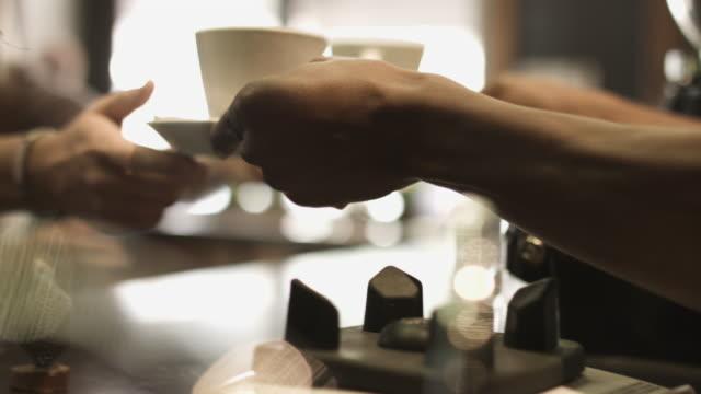 two women receive coffee, handheld - coffee shop stock videos & royalty-free footage