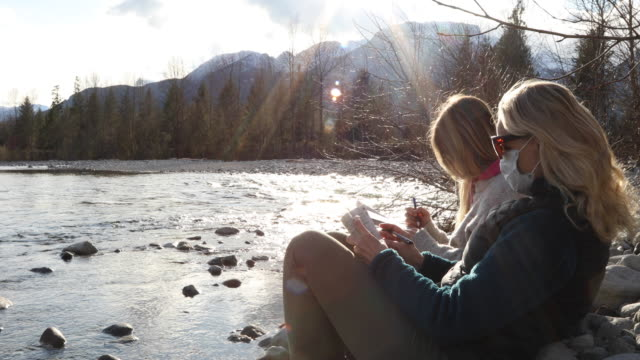two women relax on riverbank, mountains and sunlight distant - riverbank stock videos & royalty-free footage
