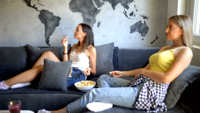 two women relaxing on sofa in the living room - concrete wall stock videos & royalty-free footage