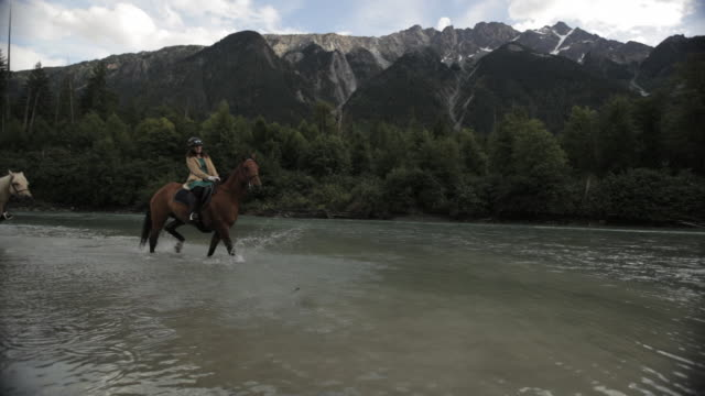 vidéos et rushes de two women ride hoses in river w/ mtn b.g. - animaux au travail