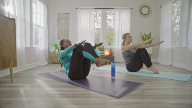 two women roll forward and back on yoga mats in sunny home studio. - pilates stock videos & royalty-free footage
