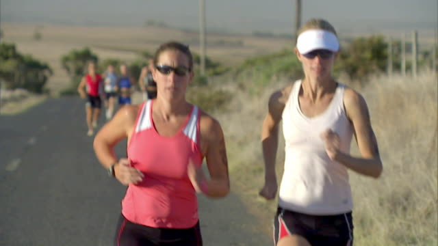 ts ms two women running ahead of group of triathletes during race / cape town, south africa - sun visor stock videos & royalty-free footage