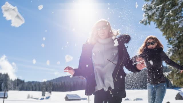 vídeos de stock, filmes e b-roll de duas mulheres correndo e brincando na neve em dia ensolarado de inverno - brincadeira de pegar