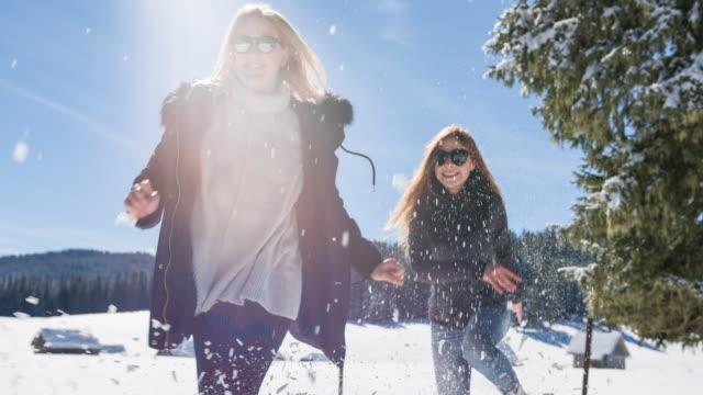 vídeos de stock, filmes e b-roll de duas mulheres correndo e brincando na neve - brincadeira de pegar